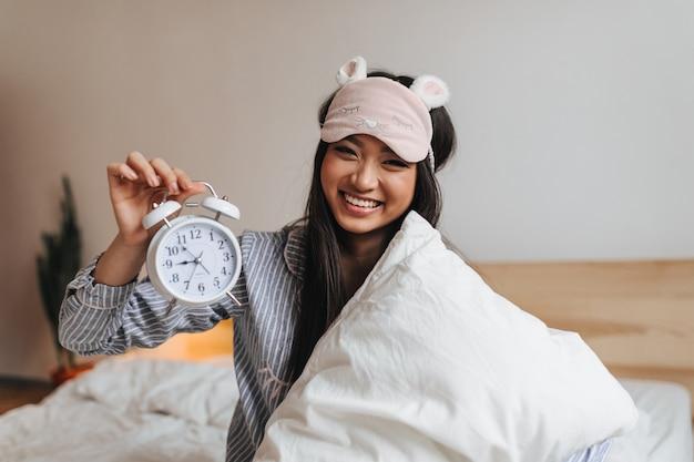 Charmante frau im gestreiften pyjama lacht und hält wecker