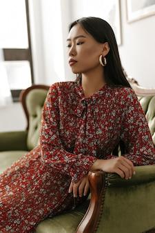 Charmante frau im roten blumenkleid sitzt auf einem klassischen samtgrünen sofa