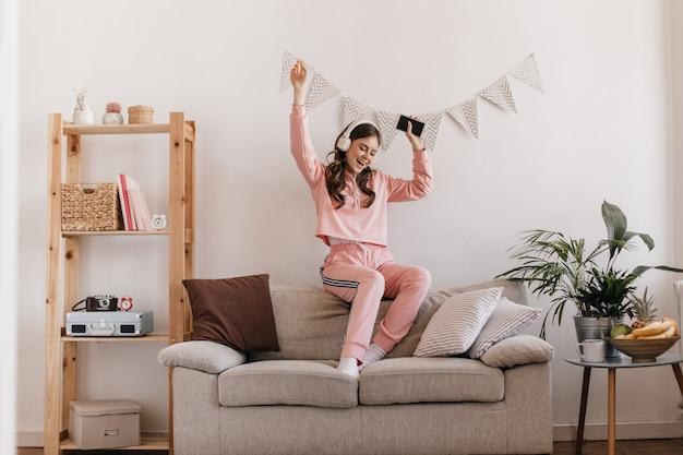 Charmante frau im trainingsanzug tanzen, auf der couch sitzen