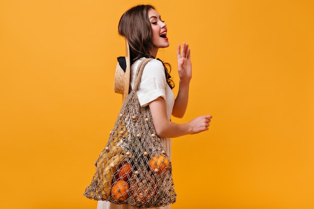 Charmante frau im weißen baumwollkleid wirft mit stringtasche auf orange hintergrund auf.