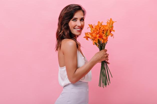 Charmante frau im weißen outfit lächelt und hält orange blumen. nette erwachsene dame im langen sommerkleid schaut in die kamera und lächelt.