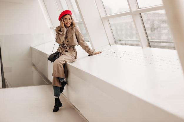 Charmante frau in beigem langem mantel und roter stilvoller baskenmütze sitzt auf fensterbank