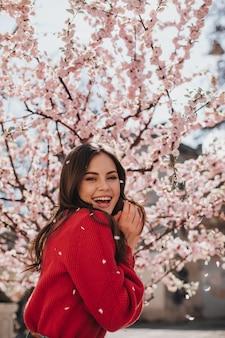 Charmante frau in hellem pullover lacht gegen blühende sakura. kühle brünette frau im roten outfit, das lächelt und frühling genießt
