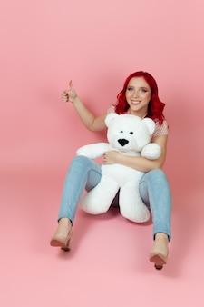 Charmante frau in jeans mit roten haaren hält einen großen weißen teddybär und gibt einen daumen hoch