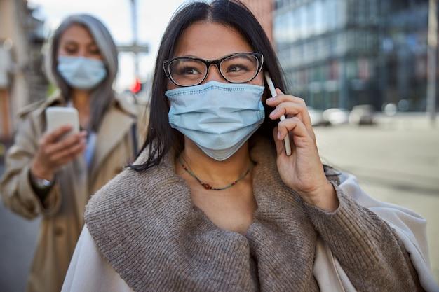Charmante frau in medizinischer maske mit telefongespräch im freien