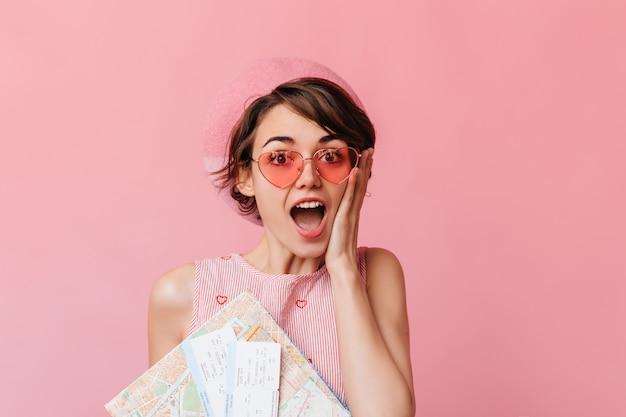 Charmante frau in rosa brille, die auf reise wartet