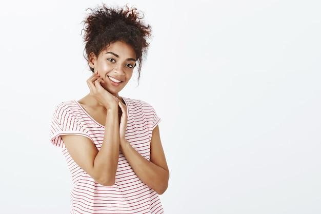 Charmante frau mit afro-frisur, die im studio aufwirft
