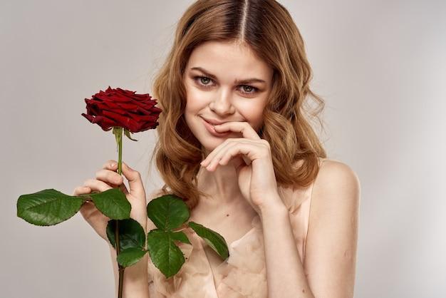 Charmante frau mit einer roten rose in der hand