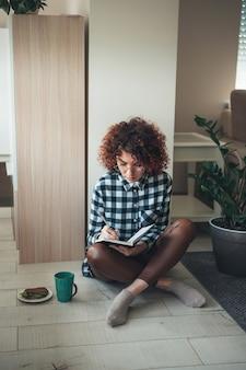 Charmante frau mit lockigem haar schreibt etwas in ein buch, während sie arbeitet und einen kaffee trinkt...