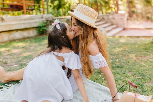 Charmante frau mit lockigen langen haaren lächelnd, während ihre tochter sie küsst. außenporträt des niedlichen kleinen mädchens, das spaß mit mutter im park mit steinstufen hat.