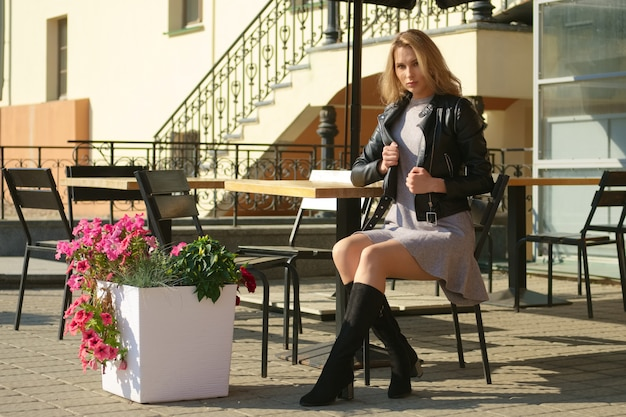 Charmante frau sitzt auf holzhocker auf offener terrasse des straßenkaffees