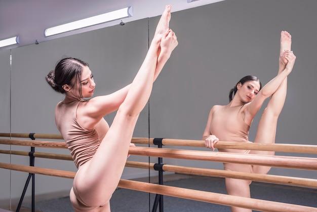 Charmante frau streckt sich in einem tanzstudio in der nähe des spiegels aus. das konzept des tanzens, ballett. professionelle ausrüstung. gemischte medien