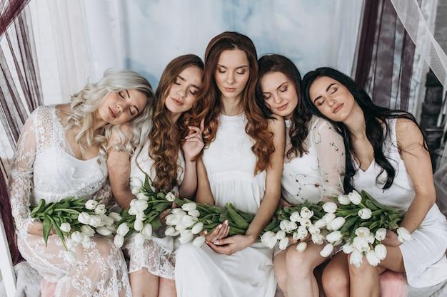 Charmante frauen sitzen seite an seite mit weißen tulpensträußen auf dem gemütlichen bett