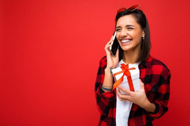 Charmante freudige emotionale erwachsene brünette frau lokalisiert über roter hintergrundwand, die weiß trägt