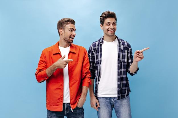 Charmante, fröhliche, bärtige männer zeigen auf den platz für text an der blauen wand. porträt eines mannes in orangefarbener jacke und seines freundes in kariertem hemd.