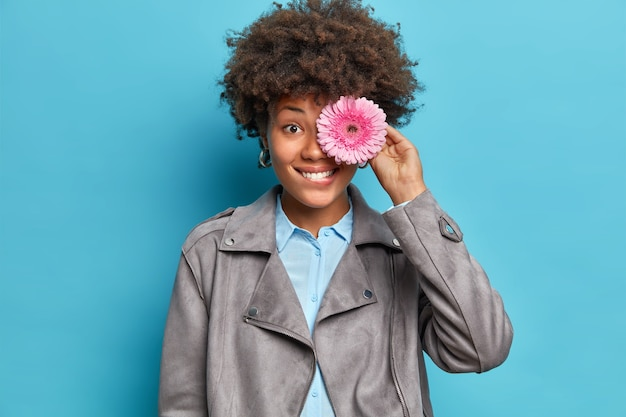 Charmante fröhliche junge frau bedeckt auge mit gerbera blume lächelt gerne gehen blumenstrauß gekleidet in stilvolle jacke über blaue wand isoliert genießt angenehmen geruch