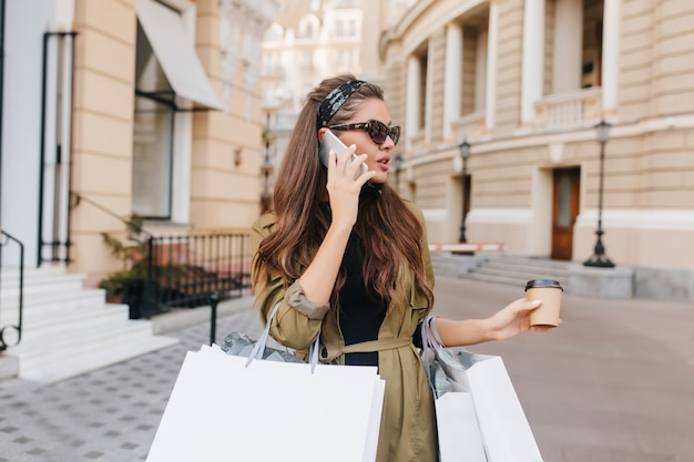 Charmante geschäftsfrau, die beim einkaufen am telefon spricht