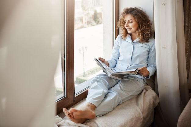 Charmante geschäftsfrau, die entspannende zeit zu hause hat. erfreute gut aussehende erwachsene frau in nachtwäsche, die auf dem fensterbrett sitzt und auf die straße schaut, modemagazin hält und über lebensstil liest