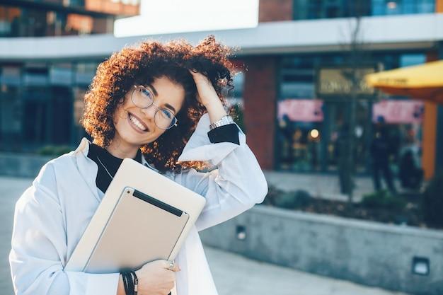 Charmante geschäftsfrau, die ihr lockiges haar berührt, während sie mit ihrem laptop draußen posiert