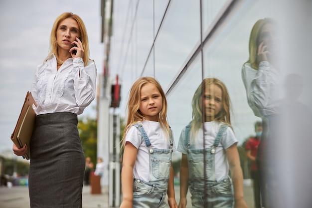 Charmante geschäftsfrau in weißer bluse und grauem rock, die mit geschäftspartnern telefoniert, während sich das kleine mädchen genervt fühlt