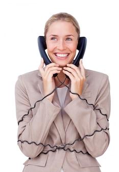 Charmante geschäftsfrau verschlungen in telefonleitungen