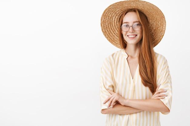 Charmante gesellige und kreative entdeckerin in gelb gestreiftem blusenstrohhut und trendigen brillen, die hände auf der brust gekreuzt halten und mit sorglosem und entspanntem ausdruck lächeln