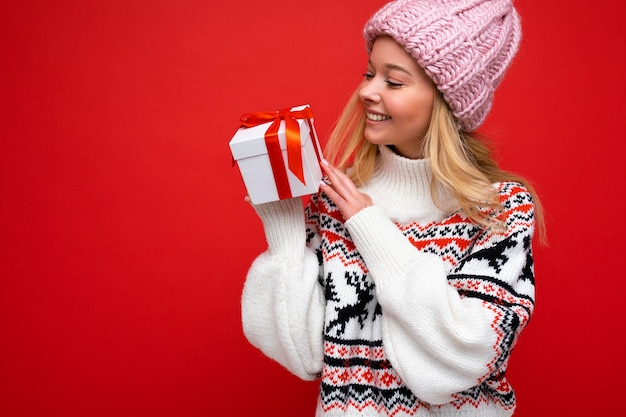 Charmante glücklich lächelnde junge blonde weibliche person isoliert über roter hintergrundwand mit winterpullover und rosa hut, die weiße geschenkbox mit rotem band hält und zur seite schaut.