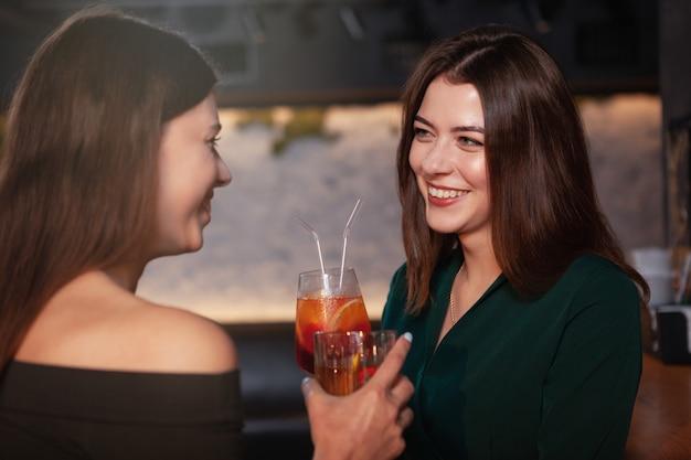 Charmante glückliche frau, die lacht und mit ihrer freundin an der bar spricht, während sie zusammen cocktails trinkt