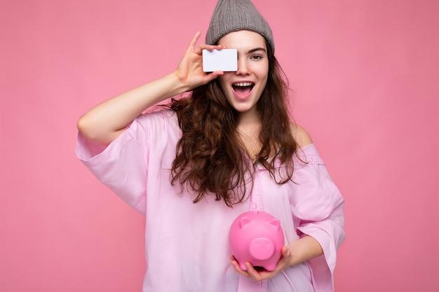 Charmante, glückliche, fröhliche junge brünette frau mit hemd isoliert auf rosa hintergrund mit freiem platz