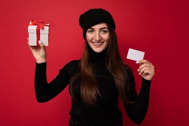 Charmante glückliche junge brünette frau mit schwarzem pullover und hut isoliert auf rotem hintergrund holding