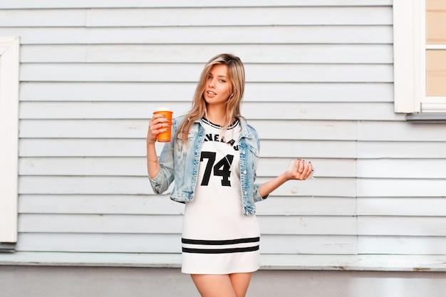 Charmante glückliche junge frau in einem stilvollen sportlichen weißen kleid in einer stilvollen jeansjacke, die nahe einem hölzernen weinlesehaus aufwirft und eine orange tasse kaffee in ihrer hand hält. fröhliches mädchen an einem sommertag.