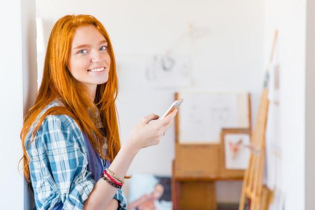 Charmante glückliche junge frau mit langen roten haaren mit smartphone in der kunstwerkstatt
