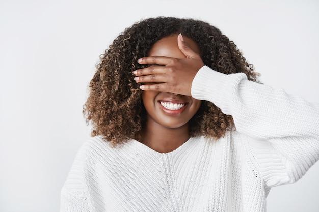 Charmante, glückliche und begeisterte süße afroamerikanische freundin, die mit der handfläche aus nächster nähe ist und ein geschenk mit einem warmen pullover über einer weißen wand vorwegnimmt