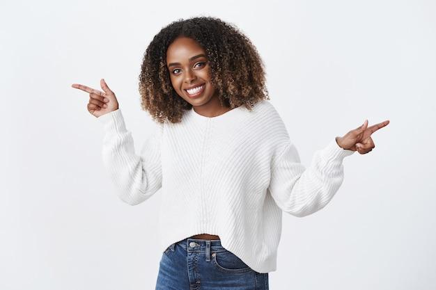 Charmante, glückliche und enthusiastische, gut aussehende dunkelhäutige frau mit lockigem haar im pullover, die süß und zärtlich lächelt und nach links und rechts zeigt, um eine vielzahl von auswahlmöglichkeiten über die weiße wand zu empfehlen