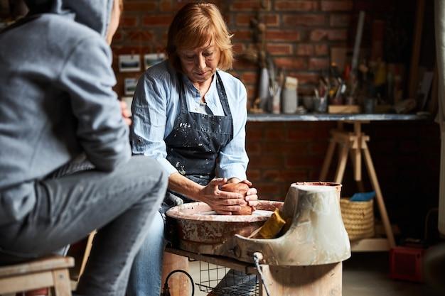 Charmante handwerkerin, die ton auf töpferscheibe knetet und formt, während student den prozess beobachtet