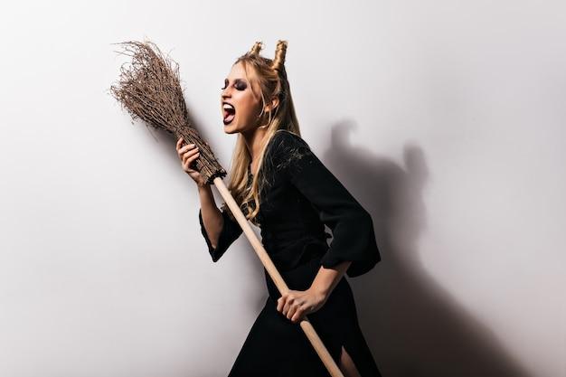 Charmante hexe in langem kleid, die mit ihrem besen tanzt. wunderschönes mädchen im vampirkostüm.