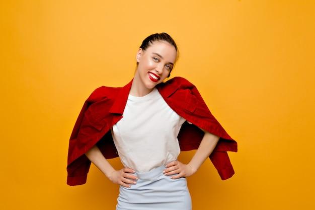 Charmante hübsche junge frau mit dem schönen lächeln, das mit gekleideter roter jacke, weißem t-shirt und blauem rock auf gelber wand aufwirft. schönes mädchen mit wahren gefühlen