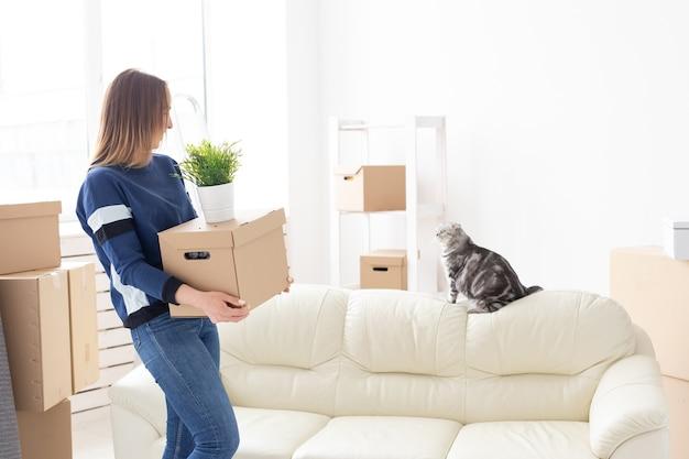 Charmante junge alleinstehende frau hält eine kiste mit dingen, während sie sich bewegt, während sie in einer neuen wohnung steht