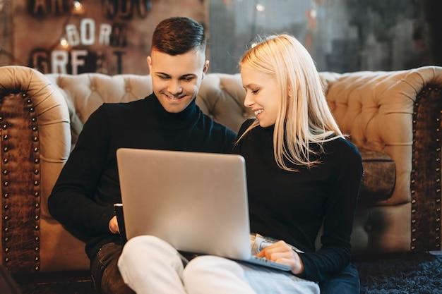 Charmante junge blonde frau hält einen laptop auf ihren beinen und schaut mit seinem freund, während sie sich auf ein sofa auf dem boden in ihrem haus stützt.