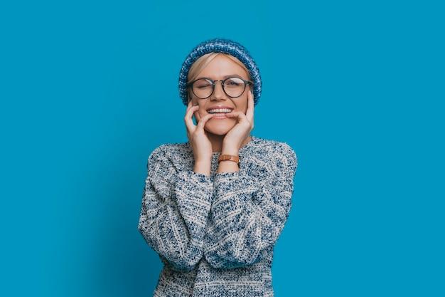 Charmante junge blonde frau in blau gekleidet brille betrachten kamera lächelnd, während er seinen finger beißt ihr gesicht mit den händen gegen die blaue wand zu berühren.