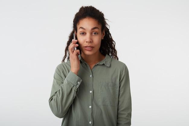 Charmante junge braune augen lockige brünette frau mit dunkler haut, die ruhig in die kamera schaut, während sie mit handy telefoniert, lokalisiert über weißem hintergrund