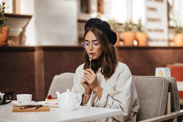 Charmante junge dunkelhaarige dame in baskenmütze, brille und beigem trenchcoat, die sich auf der sonnigen terrasse des stadtcafés ausruht, käsekuchen mit tee isst und nach unten schaut