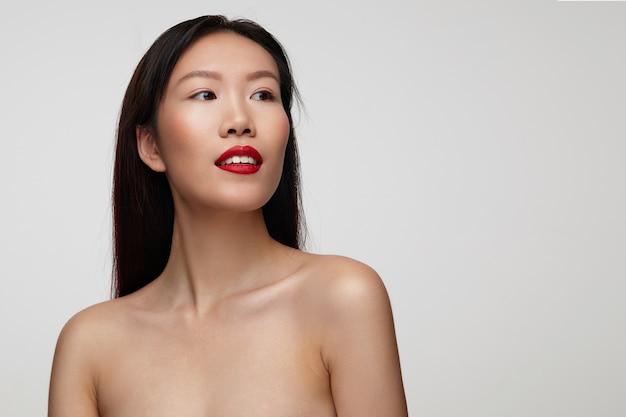 Charmante junge dunkelhaarige frau mit festlichem make-up, die mit ruhigem gesicht beiseite schaut und leicht lächelt und ihre hände unten hält, während sie über weißer wand steht