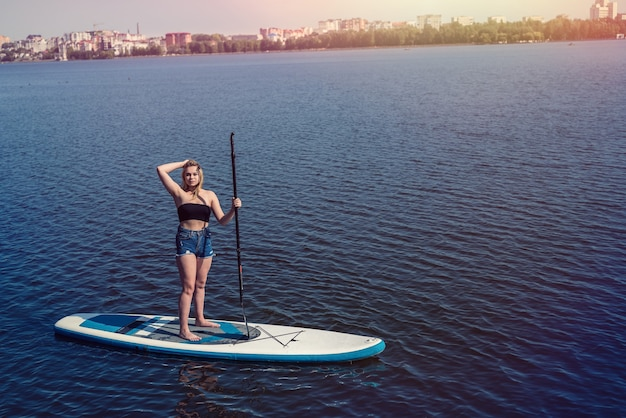 Charmante junge frau auf paddle board supam stadtsee, urlaub im sommer