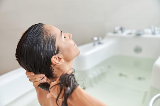 Charmante junge frau beim haarewaschen beim baden