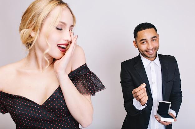 Charmante junge frau des nahaufnahmeporträts im luxuskleid mit geschlossenen augen, die auf überraschung vom gutaussehenden kerl mit ring hinten warten. valentinstag feiern, überraschung, liebe.