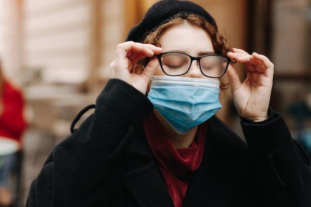 Charmante junge frau, die auf straße in der medizinischen maske mit ihrer vom atem nebligen brille geht. pandemiezeit und coronavirus.
