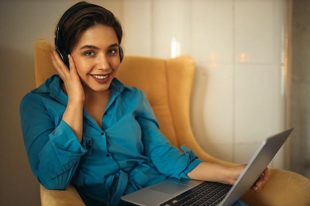 Charmante junge frau, die aus der ferne an einem tragbaren computer arbeitet und musik über drahtlose kopfhörer hört