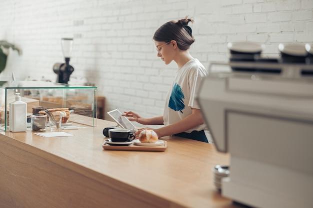 Charmante junge frau, die bestellung für kunden im kaffeehaus vorbereitet