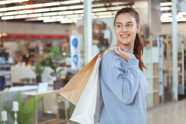 Charmante junge frau, die freudig lächelt, einkaufstaschen trägt, im einkaufszentrum spazieren geht, raum kopiert. konsumismus, einkaufskonzept